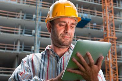 Vorarbeiter_mit_gelbem_Helm_und_Tablet