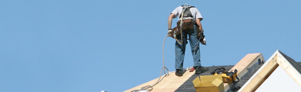 Arbeiter_mit_gelbem_Helm_auf_einem_Dach